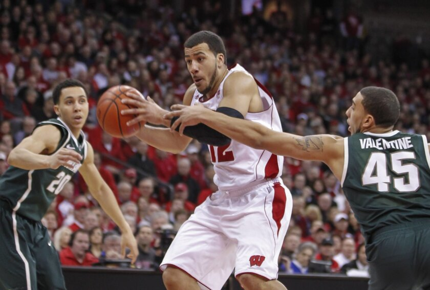 Michigan State's Denzel Valentine (45) reaches in on Wisconsin's Traevon Jackson during the second of an NCAA college basketball game on Sunday, Feb. 9, 2014, in Madison, Wis. Wisconsin upset Michigan State 60-58. (AP Photo/Andy Manis)