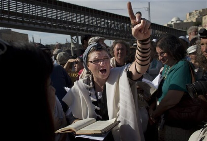 "A Jewish women from the ""Women of the Wall"" organization, leads a prayer, at the Western Wall, the holiest site where Jews can pray in Jerusalem's old city, Friday, May 10, 2013. The ""Women of the Wall"" group has been holding monthly prayer services on the first day of the Hebrew month at the Western Wall in Jerusalem for more than two decades, wearing prayer shawls and performing religious rituals reserved for men under Orthodox Judaism. Accused by ultra-Orthodox leaders of violating ""local cus"