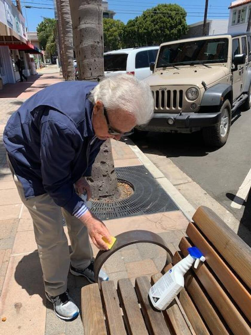 Local attorney Richard Circuit cleans off graffiti on the benches in front of some stores on Girard Avenue and Prospect Street in the Village of La Jolla.