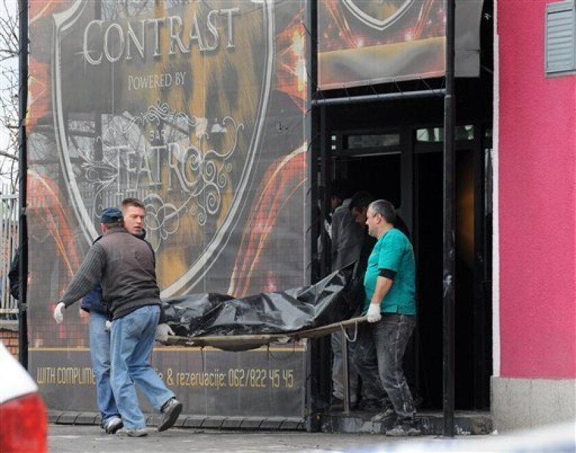 Workers remove a dead body from the nightclub Contrast in Novi Sad, Serbia, Sunday, April 1, 2012. Serbian police say six people died in a nightclub fire in the city in the country's north. (AP Photo) SERBIA OUT