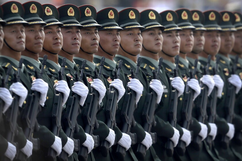 In this Oct. 1, 2019, photo, Chinese People's Liberation Army (PLA) soldiers march in formation during a parade to commemorate the 70th anniversary of the founding of the People's Republic of China in Beijing. China is increasing its defense spending by 6.8% in 2021 as it works to maintain a robust upgrading of the armed forces despite high government debt and the impact of the coronavirus pandemic. (AP Photo/Mark Schiefelbein)