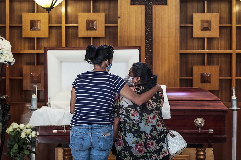 Two women stand at a casket, one with her arm around the other.