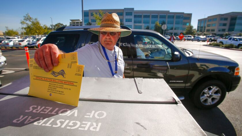 Election worker John Mann deposits mail-in ballots dropped off at the San Diego County Registrar of Voters office into a secured lock box at the drive-thru lane.