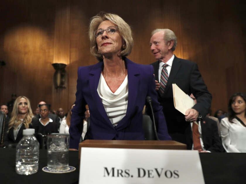 Education Secretary-designate Betsy DeVos arrives with former Sen. Joe Lieberman, right, before testifying on Capitol Hill in Washington, Tuesday, Jan. 17, 2017, at her confirmation hearing before the Senate Health, Education, Labor and Pensions Committee.