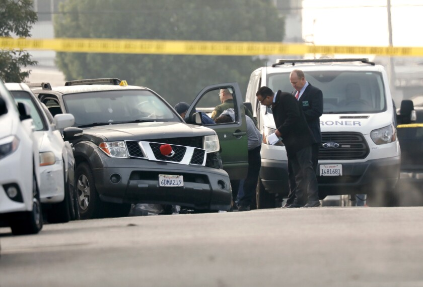 Officials study an SUV with front-end damage in a street.