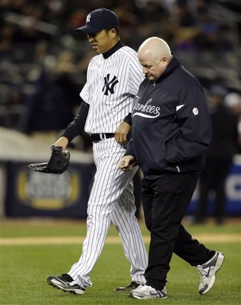 New York Yankees starting pitcher Hiroki Kuroda leaves the mound with head athletic trainer Steve Donohue during the second inning of a baseball game against the Boston Red Sox at Yankee Stadium in New York, Wednesday, April 3, 2013. (AP Photo/Kathy Willens)