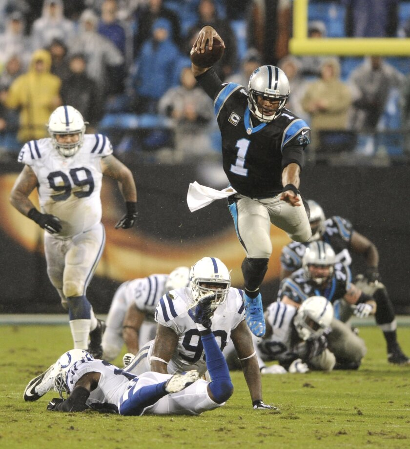 Carolina Panthers' Cam Newton (1) leaps over Indianapolis Colts players in the second half of an NFL football game in Charlotte, N.C., Monday, Nov. 2, 2015. (AP Photo/Mike McCarn)