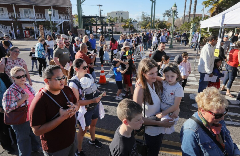 A large crowd lines up to enter a block party fundraiser in downtown Escondido to help Kaitlyn Pilsbury, owner of nearby Rosie's Cafe, who is recovering from a serious motorcycle accident.