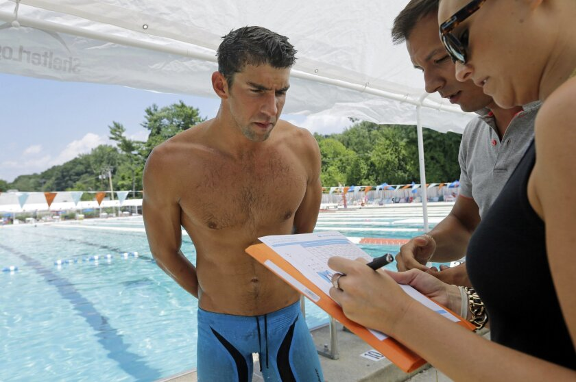 In this July 31, 2014 photo, Michael Phelps, left, goes over details of a prototype swimsuit with designers before a training session at Meadowbrook Aquatic and Fitness Center in Baltimore. After partnering with Speedo through most of his swimming career, Phelps has agreed to a new deal with Aqua Sphere. The company is a newcomer to competitive swimming, but is already designing a racing suit that Phelps can begin wearing on Jan. 1. (AP Photo/Patrick Semansky)