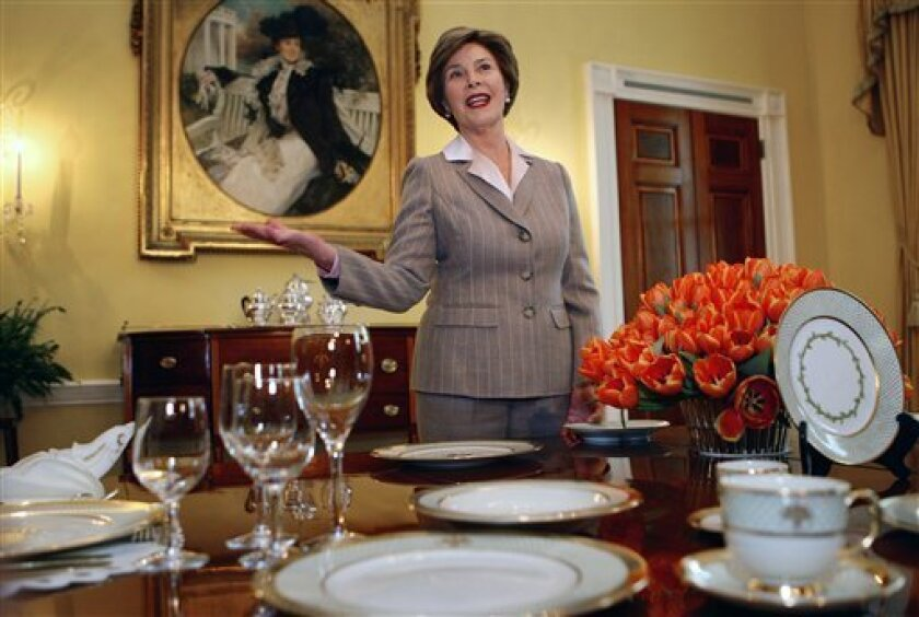 First lady Laura Bush gestures while showing off some of the new White House China Service, Wednesday, Jan. 7, 2009, in the Old Family Dining Room of the White House in Washington. (AP Photo/Ron Edmonds)