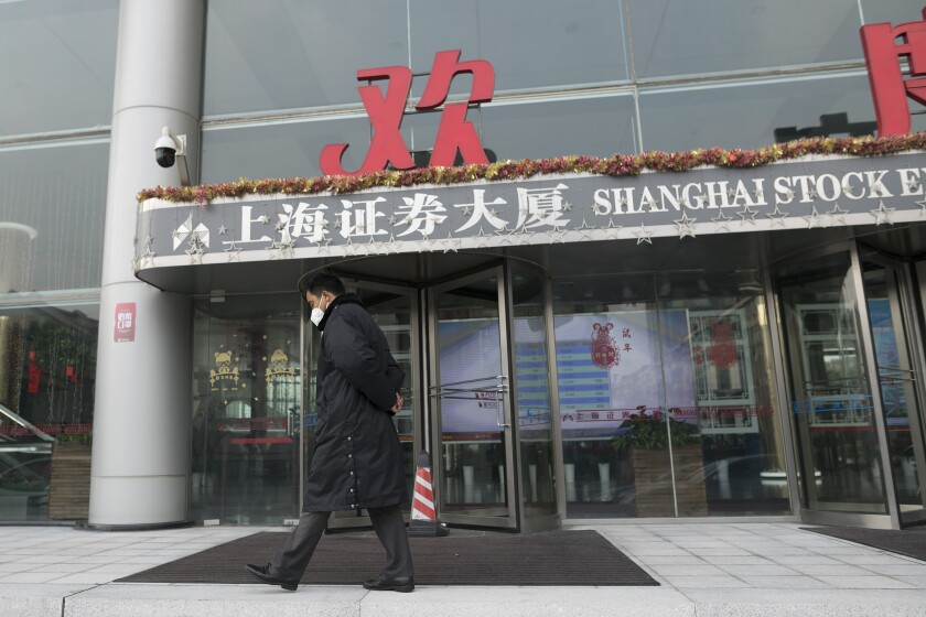 A security officer wearing a face mask walks in front of the Shanghai Stock Exchange building in Shanghai, Monday, Feb. 3, 2020. The Shanghai Composite index tumbled 8.7% Monday then rebounded slightly as Chinese regulators moved to stabilize markets reopening from a prolonged national holiday despite a rising death toll from a new virus that has spread to more than 20 countries. (AP Photo)