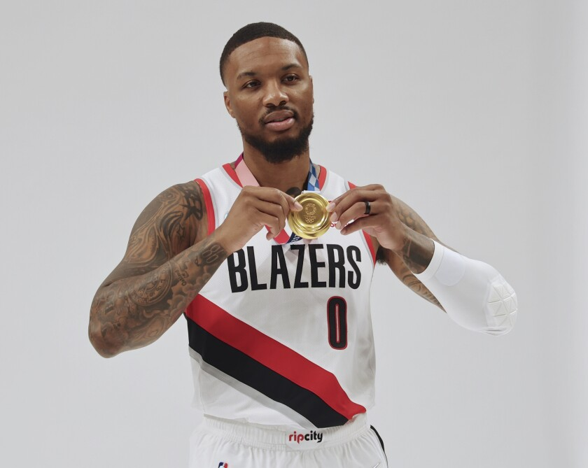 Portland Trail Blazer's Damian Lillard poses for photos with his Olympic gold medal during the NBA basketball team's Media Day in Portland, Ore., Monday, Sept. 27, 2021. (AP Photo/Steve Dipaola)
