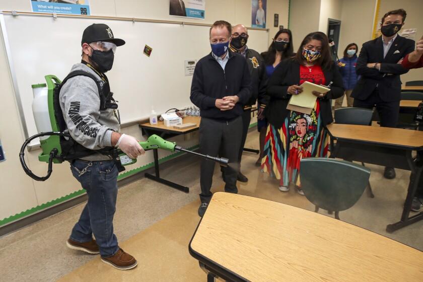 School plant manager Sergio Ruiz demonstrates the use of a electrostatic sprayer