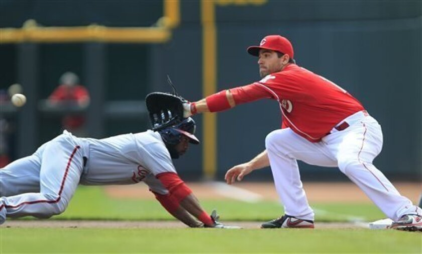 Washington Nationals' Denard Span, left, dives safely back to first base as Cincinnati Reds' Joey Votto, right, waits for a throw from pitcher Johnny Cueto in the first inning of their baseball game in Cincinnati, Sunday, April 7, 2013. (AP Photo/Tom Uhlman)