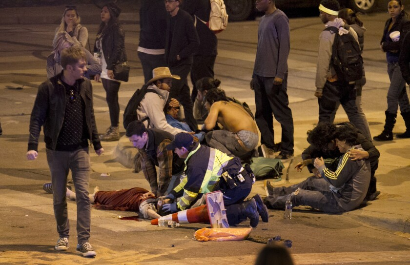 People are treated after being struck by a vehicle on Red River Street in downtown Austin, Texas, during SXSW on Wednesday. Two people died and 23 were injured.