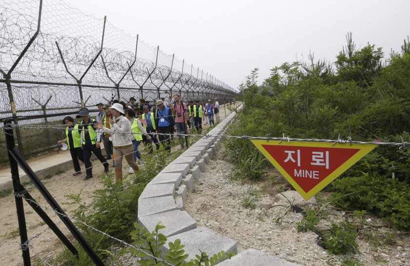 Hikers and journalists walk along the DMZ Peace Trail in the demilitarized zone in Goseong, South Ko