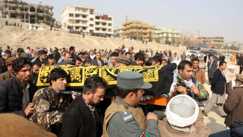 Men carry the coffin of a relative who died in Saturday's deadly suicide attack in Kabul, Afghanista
