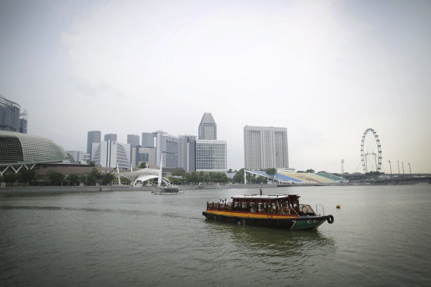In this Thursday, Nov. 5, 2015, photo, a tourist water taxi motors along the Singapore river which runs through the financial district of Singapore. On Saturday, the top officials of both sides,  Chinese President Xi Jinping and his Taiwanese counterpart, Ma Ying-jeou, flew to Singapore to sit down