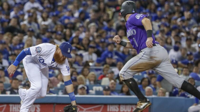 Dodgers third baseman Justin Turner misses a grounder for an error as Rockies' Garrett Hampson heads home.