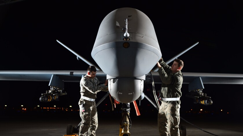 Air Force technicians prepare a MQ-9 Reaper for flight at Creech Air Force Base, Nev., in May 2014.
