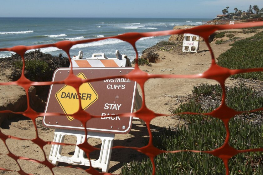 Signs and a fence warn people not to walk along a section of bluff that has eroded in Carlsbad.