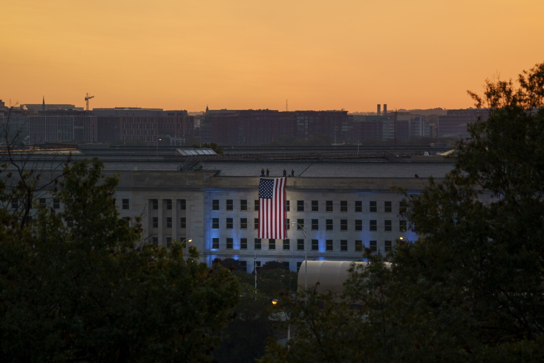 An American flag is unfurled from the roof of the Pentagon at sunrise.