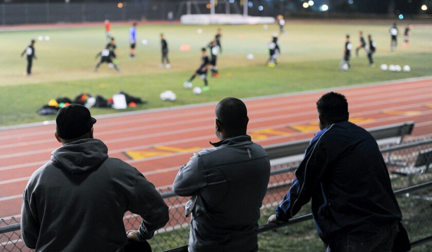 Parents watch from the stands as children work on drills at a Los Angeles Football Club soccer academy practice at Cal State L.A. on Feb. 29.