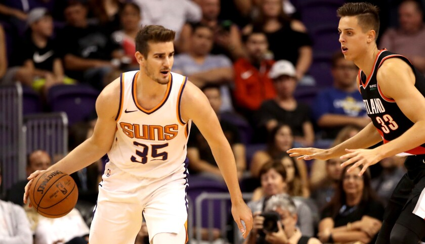 Suns forward Dragan Bender looks to drive against Trail Blazers forward Zach Collins during a game this season. Bender, the No. 4 pick in the 2016 draft, rarely plays.