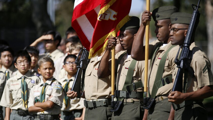 Boy Scouts watch as the Marine color guard participates in a ceremony honoring the fallen heroes.