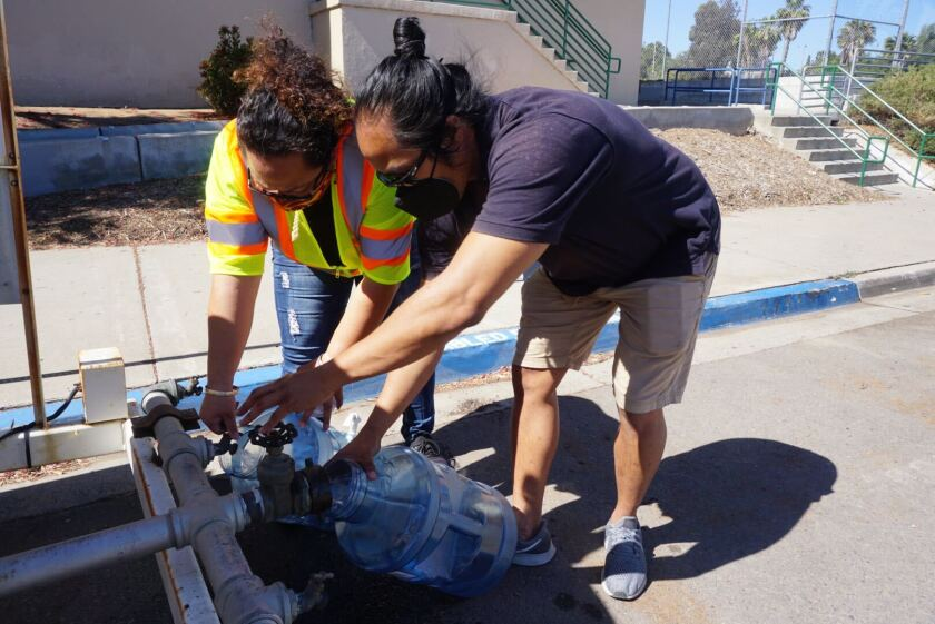 Volunteers at the Encanto Recreation Center fill containers with fresh water for residents in the area.