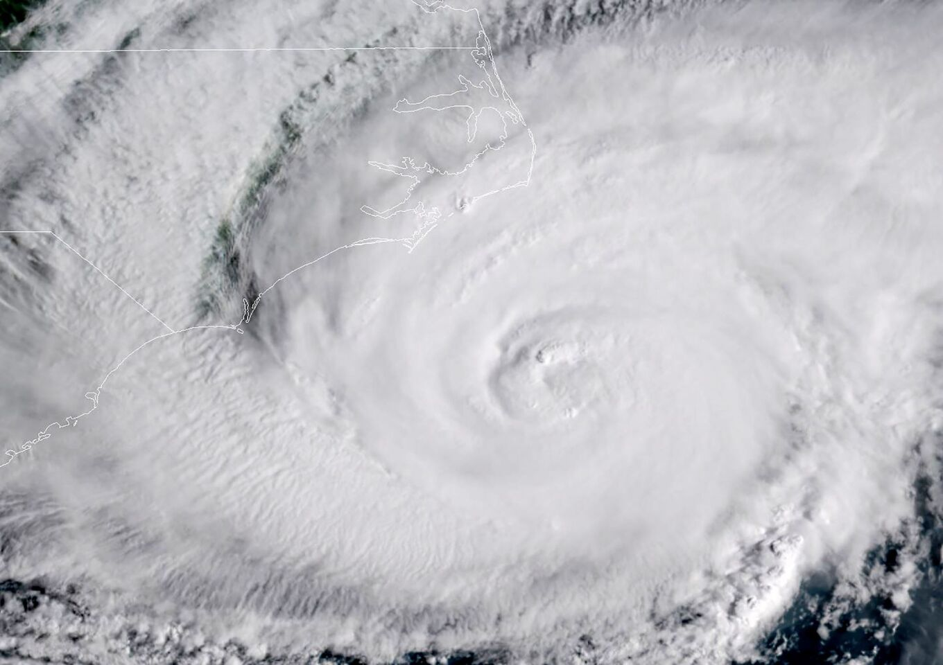 """This NOAA/RAMMB satellite image taken at 13:15 UTC on September 13, 2018, shows Hurricane Florence beginning to hit the US east coast. - Florence edged closer to the east coast of the US Thursday, with tropical-force winds and rain already lashing barrier islands just off the North Carolina mainland. The huge storm weakened to a Category 2 hurricane overnight, but forecasters warned that it still packed a dangerous punch, 110 mile-an-hour (175 kph) winds and torrential rains. (Photo by Jose ROMERO / NOAA/RAMMB / AFP) / RESTRICTED TO EDITORIAL USE - MANDATORY CREDIT """"AFP PHOTO / NOAA/RAMMB"""" - NO MARKETING NO ADVERTISING CAMPAIGNS - DISTRIBUTED AS A SERVICE TO CLIENTSJOSE"""