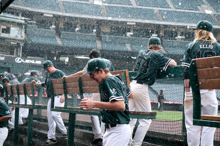 Costa Mesa High School players head under cover as rain and hail comes down in the 3rd annual Halo C