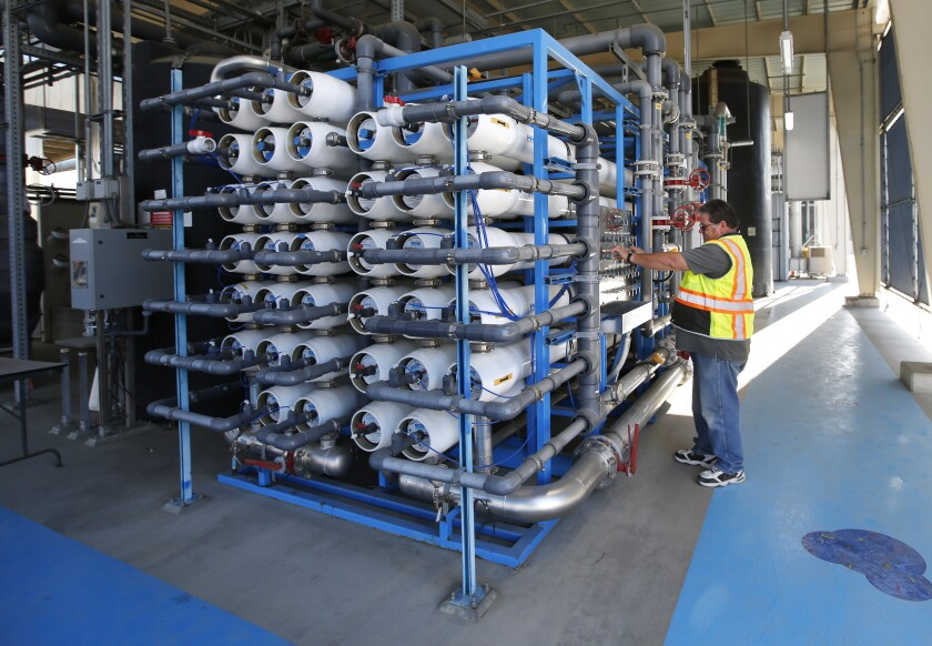 Senior plant tech supervisor David Mills looks over reverse osmosis filters at the Pure Water Demonstration Facility.