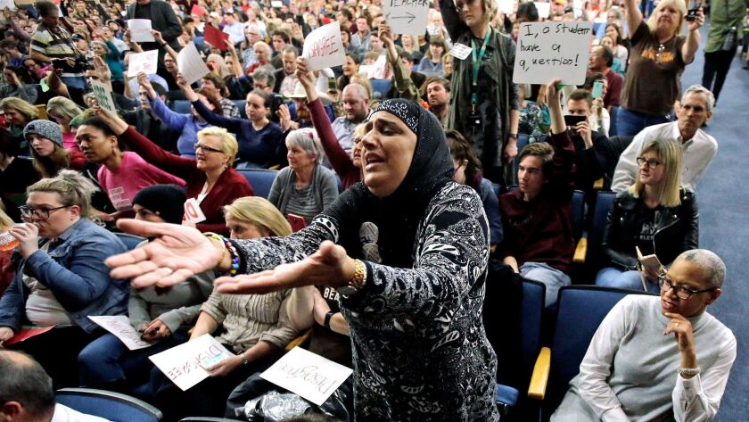 A woman reacts during a discussion of President Trump's travel ban at a town hall meeting at in Cottonwood Heights, Utah.