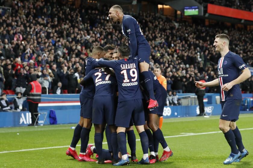 PSG players celebrate after Edinson Cavani scored their fourth goal during the League One soccer match between Paris Saint Germain and Lyon at the Parc des Princes stadium in Paris, Sunday, Feb. 9, 2020. (AP Photo/Thibault Camus)