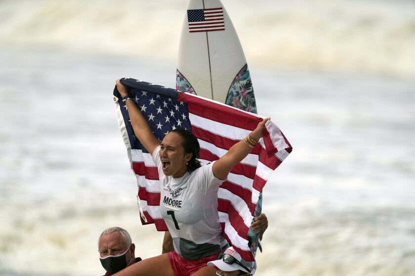 Carissa Moore holds up a U.S. flag while a surfboard is behind her