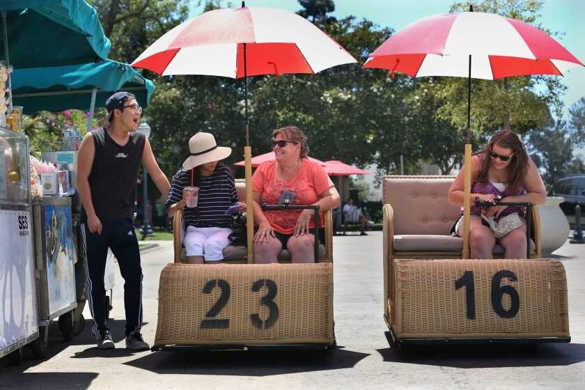 David Cho, left, Sofia Cho (in the hat), and friends Julie Rodriguez and Janel Rodriguez prepare to take their rented Electriquettes on a spin through Balboa Park. The electrically-powered wicker carts are fashioned after the carts used in the park during the 1915-1916 Panama-California Exposition.