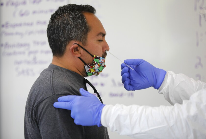 Memo Aguilar gets a COVID-19 test at Cal State University San Marcos, one of the busiest testing centers in San Diego County.