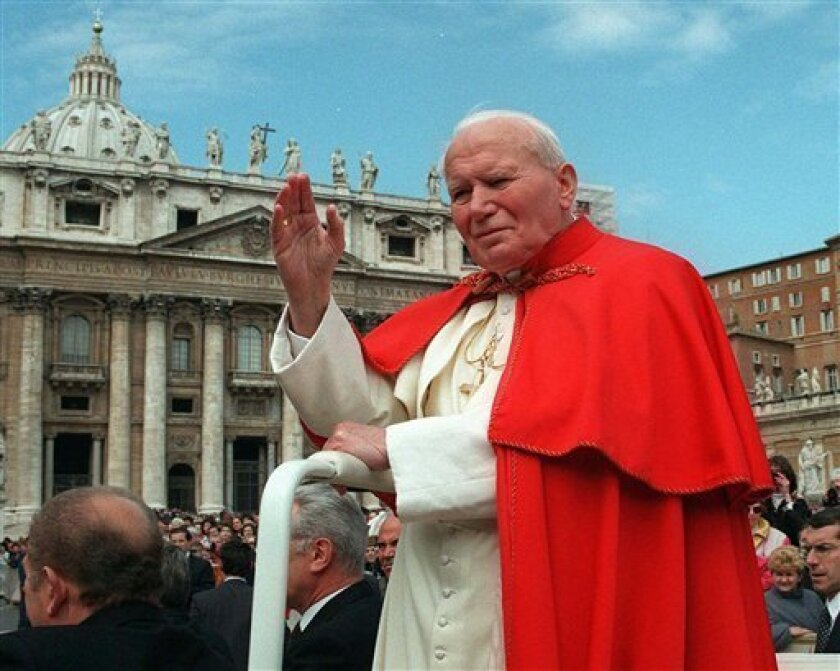 FILE - In this file photo taken on April 23 1997, Pope John Paul II waves to faithful as he crosses St. Peter's square at the Vatican. Popes John Paul II and John XXIII will be declared saints on April 27, 2014. Pope Francis announced the date Monday, Sept 30, 2013,  during a meeting with cardinals