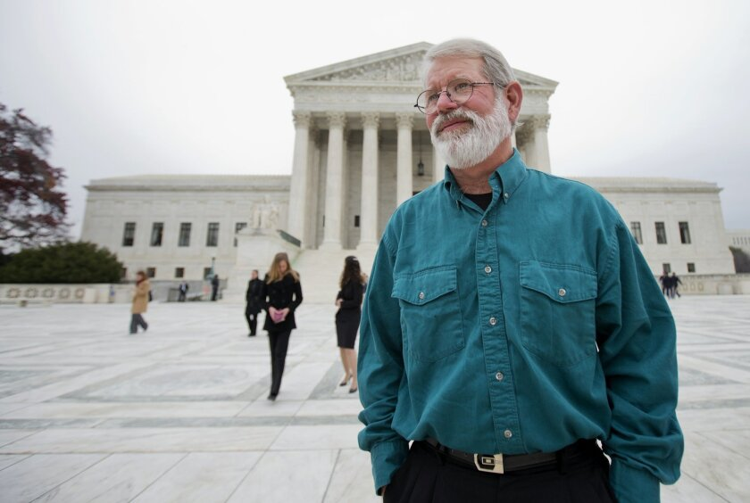 John Dennis Apel, stands in front of the Supreme Court in Washington, Wednesday, Dec. 4, 2013, following an argument on the right to protest at a military base. Apel had been barred from entering any part of Vandenberg Air Force Base on the central California coast, including the protest area on a public highway that passes near the main gate. (AP Photo/Manuel Balce Ceneta)