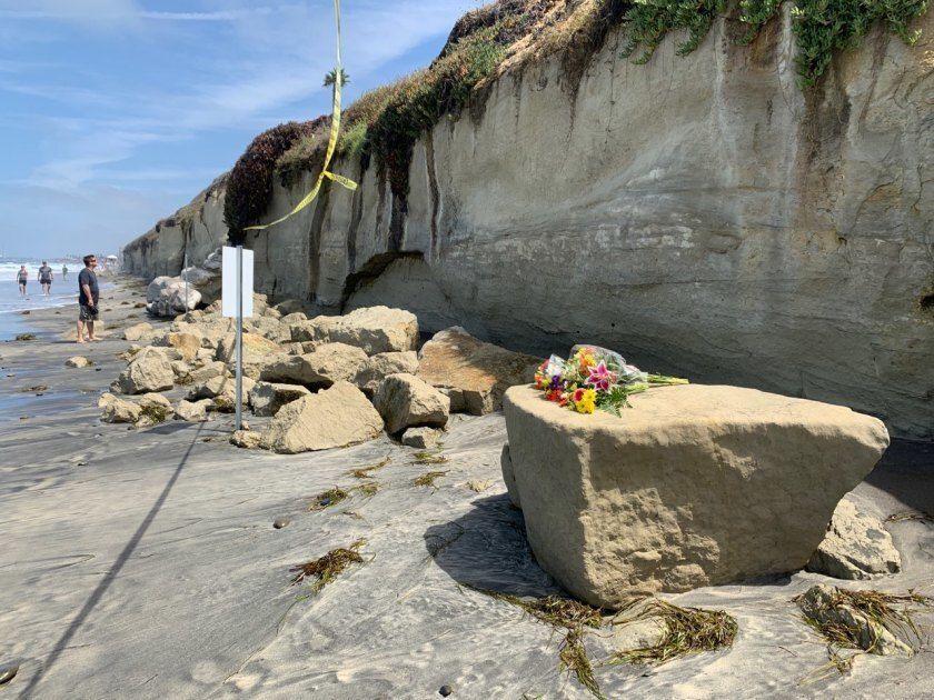 Flowers are left for victims of the bluff collapse in Encinitas.