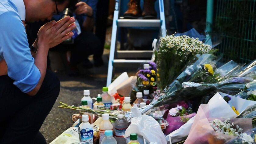 A man pays his respects at the crime scene where a man stabbed 19 people, including children, in Kawasaki, Japan, on May 28.
