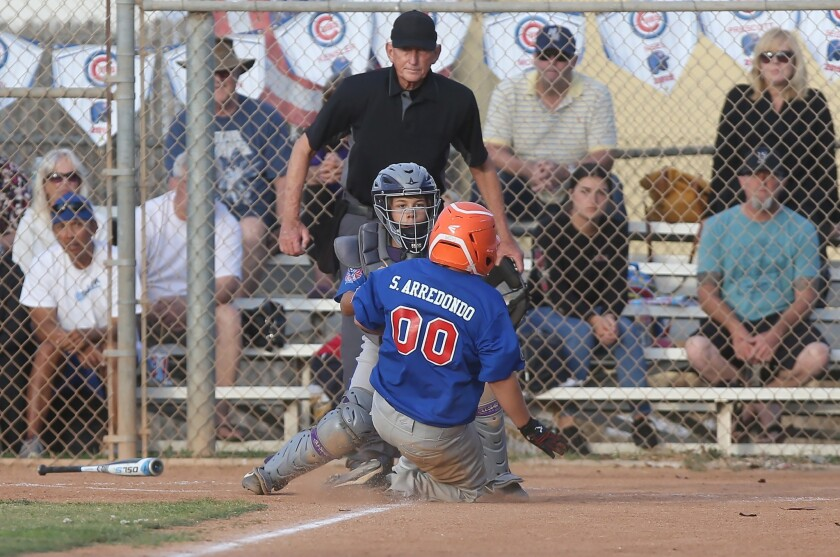 Costa Mesa Dodger catcher Sawyer Atkinson tags out Samuel Arredondo (00) during a District 62 Tourna