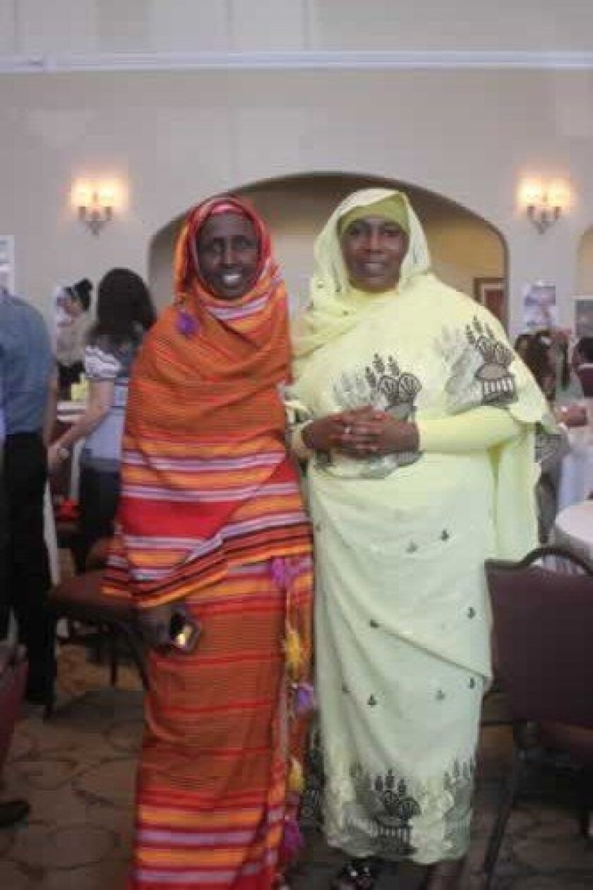 Some members of the audience dress in traditional garb from their countries. in this photo are Maha hussein (left) in an Alindi from Somalia and Fatima Abdelvahman in a Toob from the Sudan.