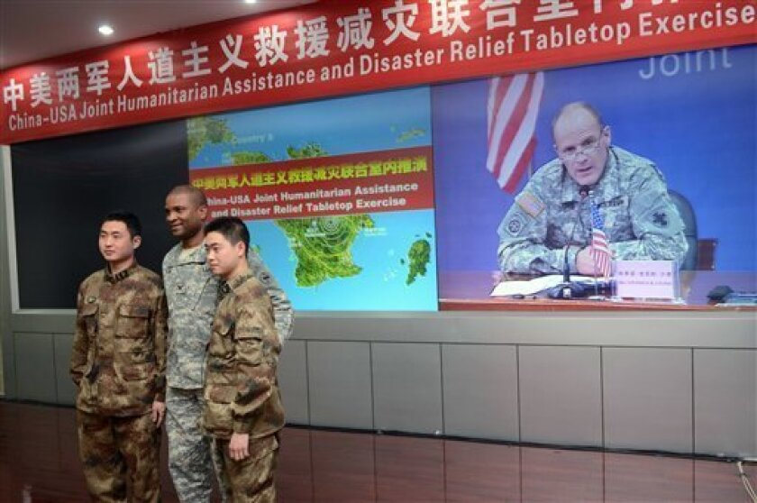 A U.S. army soldier, center, and two People's Liberation Army (PLA) soldiers pose for photos as U.S. Major General Stephen Lyons of the U.S. Army Pacific speaking at a press conference is shown on a screen at the end of a two-day military exercise at a PLA facility in Chengdu in China's southwest S