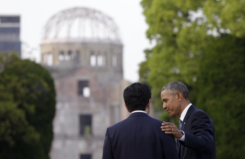 FILE - In this May 27, 2016 file photo, U.S. President Barack Obama, right, and Japanese Prime Minister Shinzo Abe speak with the Atomic Bomb Dome seen at rear at the Hiroshima Peace Memorial Park in Hiroshima, western Japan. (AP Photo/Carolyn Kaster, File)