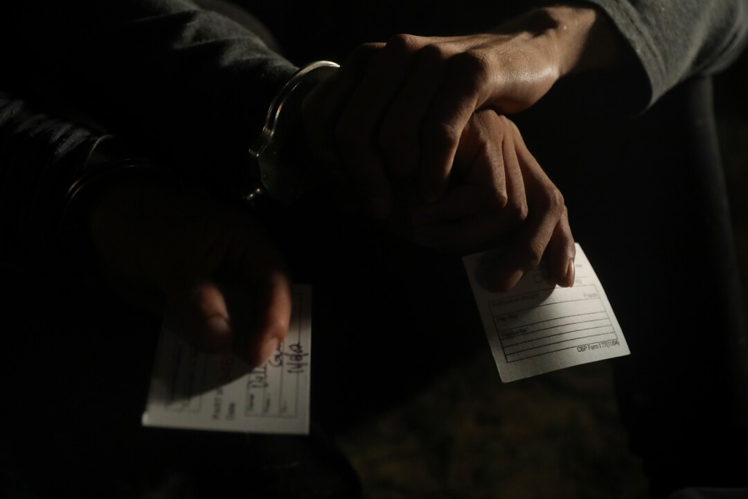 Handcuffed migrants hold processing cards