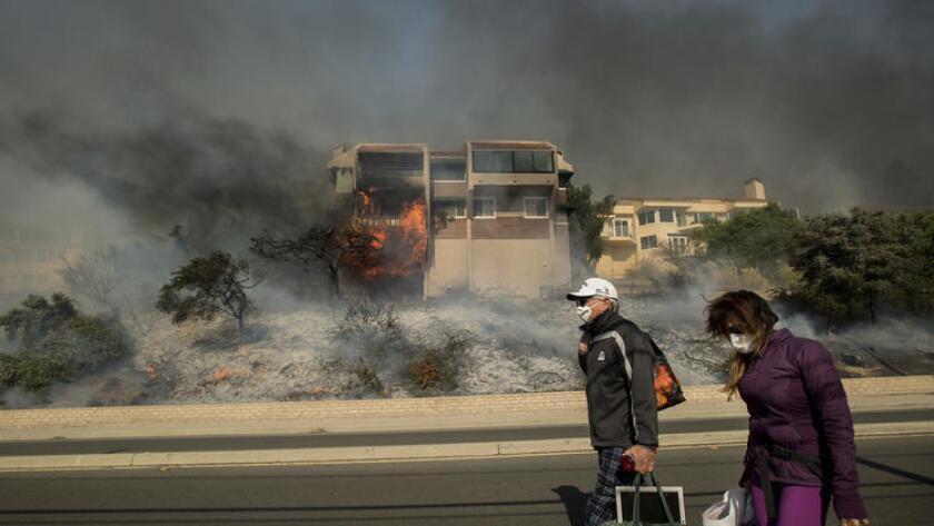James y Josie Ralstin sacan sus pertenencias de su casa ubicada en el condado de Ventura, California, mientras las llamas consumen otra residencia el martes 5 de diciembre de 2017. (AP Foto/Noah Berger)
