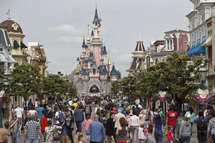 Visitors walk toward the Sleeping Beauty's Castle at Disneyland Paris.