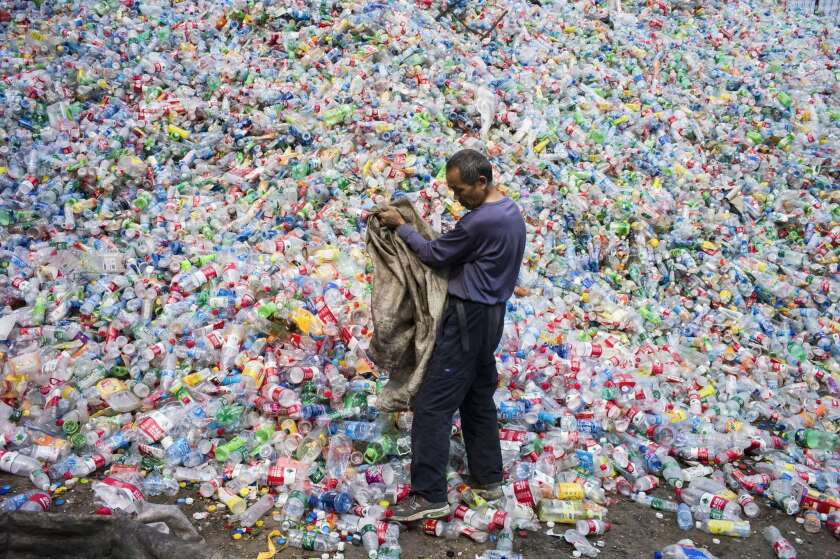 A Chinese laborer sorts plastic bottles for recycling in Dong Xiao Kou village near Beijing on Sept. 17, 2015. China is the world's biggest emitter of greenhouse gases that cause climate change, and a crucial player in the global gathering outside Paris.